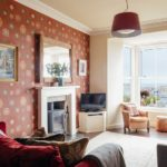 Living room of 6 Barnoon Terrace, St Ives with wood burner and sea views