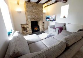 Longdrift living area with woodfire and corner sofa